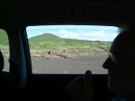 View from car of lava landscape and buried houses.
